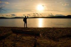 远足者人黑暗的运动服的和有站立在海滩的运动的背包的,放松和享受日落在天际 不可思议的秋天da 免版税图库摄影