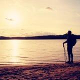 远足者人黑暗的运动服的和有站立在海滩的运动的背包的,放松和享受日落在天际 不可思议的秋天da 库存照片