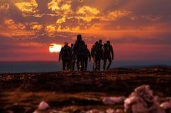 远足者伸手可及的距离在日落的山上面 图库摄影