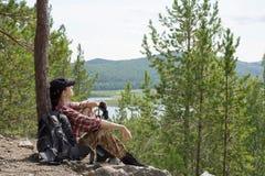 远足者侧视图坐在小山的地面在与packback和双筒望远镜的树中 库存图片