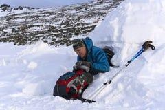 远足者倾吐自己从热水瓶的一份热的饮料,坐在一座多雪的房子园屋顶的小屋 免版税库存图片