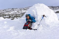 远足者倾吐自己从热水瓶的茶,坐在一座多雪的房子园屋顶的小屋 库存图片