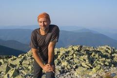 远足者其余岩石上面在一个美妙的晴朗的早晨 免版税库存照片