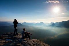 远足者和照片热心者和在峭壁和认为的三脚架呆在一起 梦想的老保守风景,在一个美丽的谷的蓝色有薄雾的日出 图库摄影
