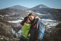 远足者和照相机夫妇有背包的在山峭壁的 免版税库存照片