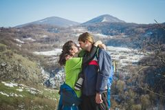 远足者和照相机夫妇有背包的在山峭壁的 免版税图库摄影