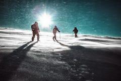 远足者和降雪在冬天山 库存图片