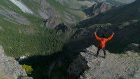 远足者在一个岩石顶部用他的被举的手享受晴天空中慢动作4k 股票视频