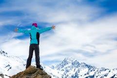 远足者在一个岩石顶部用他的被举的手 免版税图库摄影