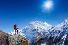 远足者在与背包的一个岩石顶部享受晴天 库存照片