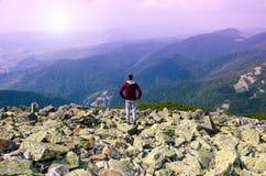 远足者在与背包的一个岩石顶部享受晴天 免版税库存照片