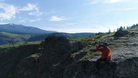 远足者在峰顶站立并且通过双筒望远镜空中慢动作4k享受风景 影视素材