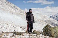 远足者在雪山小山停留并且享受美丽的景色 库存照片