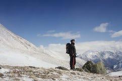 远足者在雪山小山停留并且享受美丽的景色 免版税库存图片
