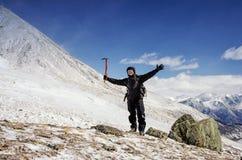 远足者在雪山小山停留并且享受美丽的景色 免版税库存照片