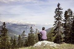 远足者坐在山上面的岩石在高山风景 免版税库存照片