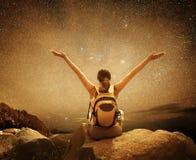 远足者坐在山和享受夜空视图顶部与 免版税库存照片