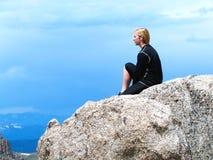 年轻远足者坐岩石 库存照片