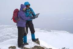 远足者夫妇一个冬天山峰的与膝上型计算机 免版税库存照片