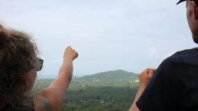 年轻远足者夫妇指向和谈话有在山热带森林酸值Phangan美好的风景的看法  股票录像