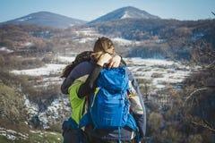 远足者夫妇有看在山景的背包的 免版税库存图片