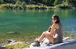 远足者女孩在与山拐杖的一块石头摆在 免版税图库摄影