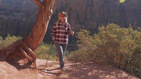 远足者妇女在迁徙的小径走锡安峡谷的红色岩石 股票录像