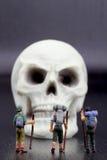 远足者微型小雕象和人的头骨 免版税图库摄影