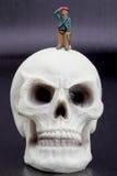 远足者微型小雕象和人的头骨 免版税库存图片