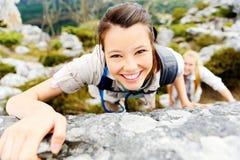 远足者微笑,当攀登岩石墙壁时 免版税库存照片