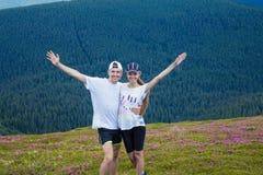 远足者愉快的夫妇拥抱在美丽的山的爱的 图库摄影