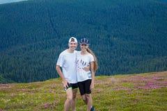 远足者愉快的夫妇拥抱在美丽的山的爱的 免版税库存图片