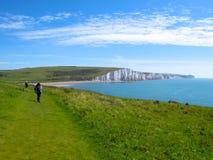 远足者接近七个姐妹,东萨塞克斯郡,英国白色峭壁  免版税库存图片