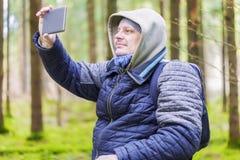 远足者摄制与片剂个人计算机在森林里 库存图片
