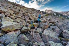 远足者攀登山岩石倾斜在阿尔泰山的, 免版税库存照片