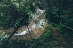 远足者旅客探险家攀登在瀑布背景支持锻炼极端旅行概念的小山 库存图片