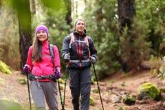 远足者步行在森林里的夫妇背包徒步旅行者 免版税库存图片