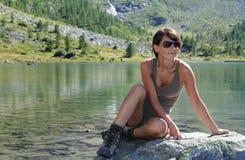 远足者由一个高山湖的女孩姿势 免版税库存图片