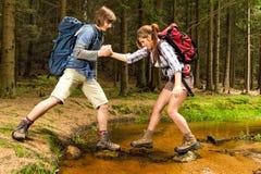 远足者男孩帮助迁徙的女孩横穿小河 免版税库存图片