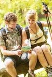远足者背包徒步旅行者夫妇在旅行的读书地图 库存图片