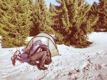 远足者设备为雪靴旅行做准备 冬天在多雪的山的少量天艰苦跋涉 浅绿色帐篷,背包和别的 库存图片