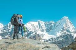 远足者谈论旅行溃败在高山 图库摄影
