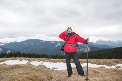 远足者谈话在冬天山的智能手机 免版税库存图片