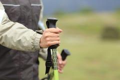 远足者递拿着一根远足的杆,当走时 免版税库存图片