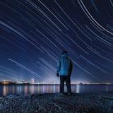 远足者,站立在河岸和享受天空的夜视图 免版税库存照片