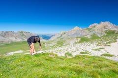 远足者读书迁徙的地图,当休息在全景山斑点时 户外活动、夏天冒险和探险在 免版税图库摄影