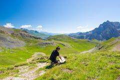 远足者读书迁徙的地图,当休息在全景山斑点时 户外活动、夏天冒险和探险在 库存图片