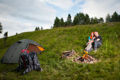 远足者结合坐草在帐篷和营火附近 图库摄影