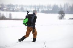 远足者-有背包的人走在多雪的领域的 免版税库存图片