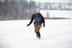远足者-有背包的人走在多雪的领域的 库存图片